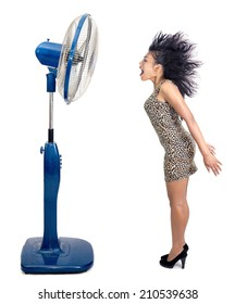 Electric fan blowing wind at a screaming woman with flying hair. A woman stands near a big fan isolated on white background. Woman blowing the hair from the air flow from the fan.