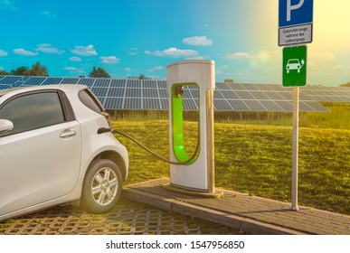 """Electric filling station electric car white solar system translation parking lot sign: """"electric vehicles during charging"""" (German)"""