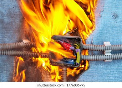 Electric fire caused by a short circuit in home electrical network. Damaged wiring caused overload of power system in house. Burned insulation of the electrical wires. The junction box ignited.
