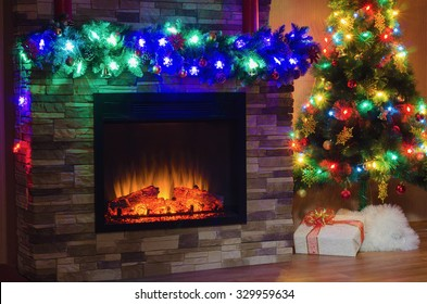 Electric fireplace and Christmas tree, decorated with garlands with colored lights