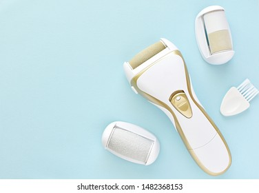 Electric foot and nail file, top view on blue background, feet care.