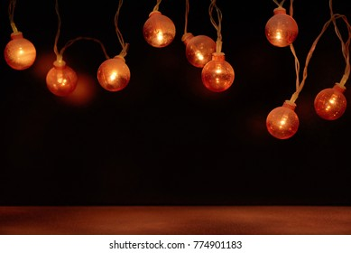 Electric garland with red light bulbs covered with frost on a black background.