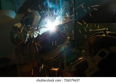 Electric Gas Welder working with sparks steel welding gloves.