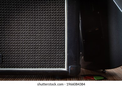 Electric guitar amp with blurred guitar leaning on it. A few picks next to amp.