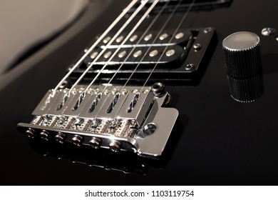 Electric guitar close-up black. Separate elements, strings, pickups. Background in blur.