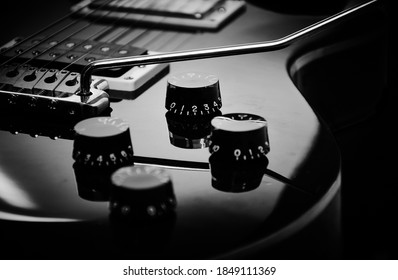 Electric guitar closeup and isolated on black background. Musical instrument in black and white with tremolo and details.