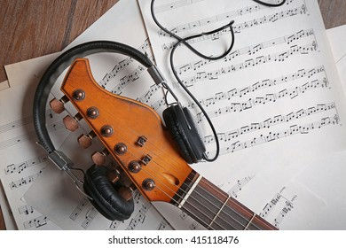 Electric guitar and headphones with music notes on wooden background, close-up