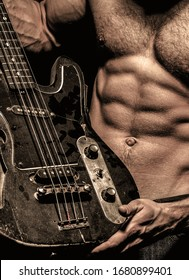 Electric guitar. Guitar. Instrument on stage and band. Strong, muscular, muscles man, bodybuilding. Music concept. Torso man. Play the guitar Chest muscles