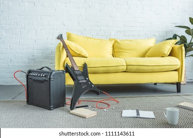 electric guitar, loud speaker, smartphone, books and cup of coffee on floor near yellow sofa in living room