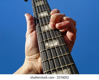 Electric guitar neck against blue sky background.