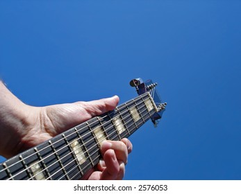 Electric guitar neck against blue sky background with space for text at top.