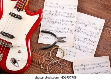 Electric guitar with notes, pliers and strings on wooden background