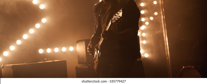 Electric guitar player on a stage with back scenic illumination, soft selective focus