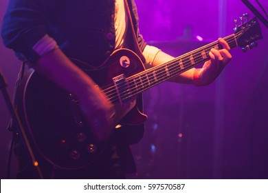 Electric guitar player on stage with purple scenic illumination, soft selective focus