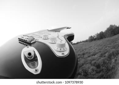 An electric guitar presented in fisheye black and white