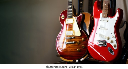 Electric guitars resting on a guitar stand in a darkish room or studio, with plenty of copy space.Shallow depth of field.
