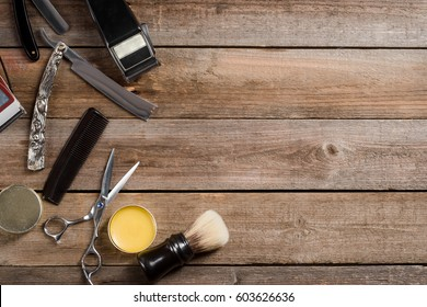Electric hair trimmer, vintage straight razors, a comb, wax and brush on the wooden background, close-up. Place to insert your text. Hipster grooming.