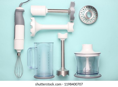 Electric hand mixer. Set of nozzles and  containers for blender on blue background. Top view, flat lay
