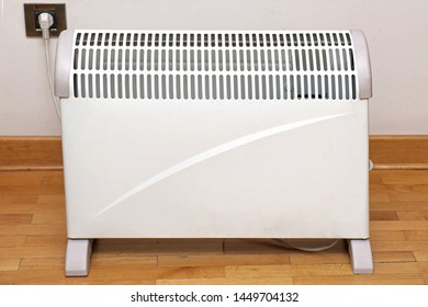 Electric heater on wooden floor inside interior and plugged into socket on a wall