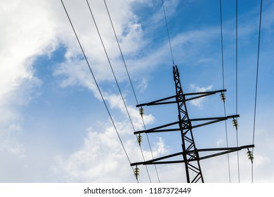 Electric high voltage transmission pole power line and wires with cloudy blue sky.
