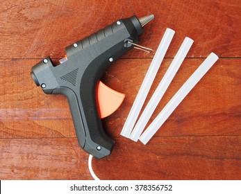 Electric hot glue gun on a wood background