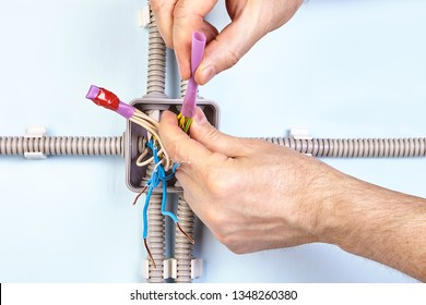 Electric installation work, Electrician puts heat shrinkable tube on copper wiring, heat shrink tubing insulates, provide strain relief, and protects against mechanical damage and abrasion.