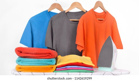 Electric iron and tidy clothes on the iron board isolated over white background