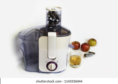 Electric juicer with used batteries instead of fresh fruits or vegetables, white background, ecological problem, earth pollution caused by wrong dispose of electronic equipment, focus on batteries