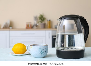 Electric kettle, cup of tea and lemon on kitchen table