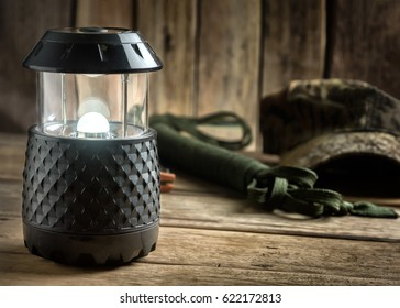 Electric Lamp and Hiking Equipment on Wooden Table.