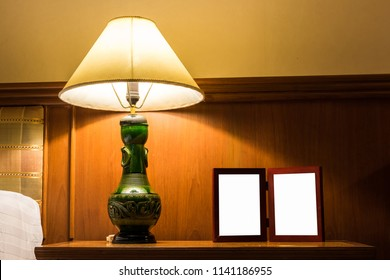 Electric lamp and picture frame on bedside table in bedroom.