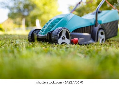 Electric lawn mower cuts moss and green grass. The alignment of the green lawn with the mower. Close-up in front of a green lawn mower on wheels on the background of the garden