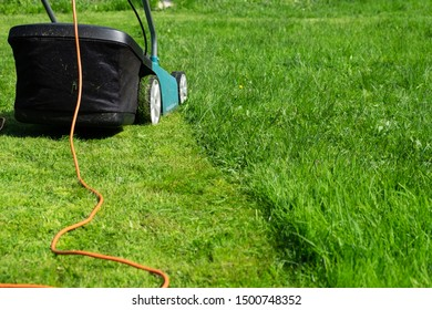 Electric lawn mower on a standing lawn