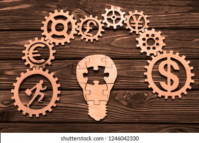 electric light bulb made of wooden puzzles, gears on a wooden table background. people, signs the exchange of money. business vision.