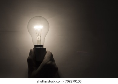 Electric light bulb shining and hand held.