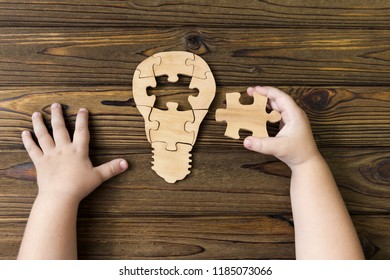 electric light bulb from wooden puzzles with missing element, human hands on a wooden background. creativity, ideas, education.