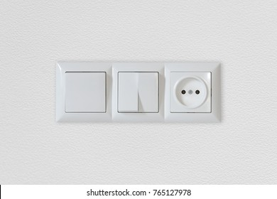 Electric light switch and socket on the empty wall, electrical power socket and plug switched