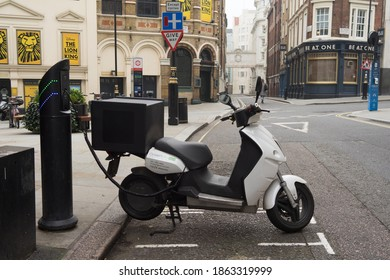 Electric moped charging at a charging point in the street. London - 28th November 2020