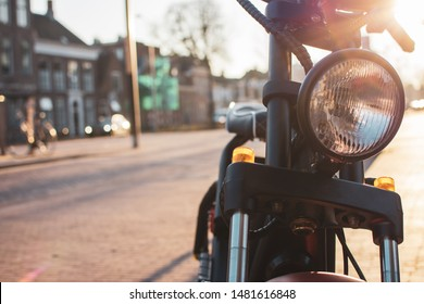An electric moped on the sidewalk in the city, in the background is a street view with buildings by sunset.