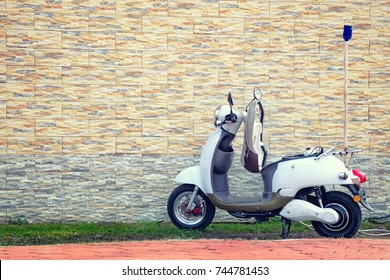 Electric motor scooter parked near a beautiful wall for charging. Empty copy space for text.