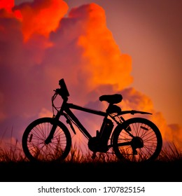 Electric Mountain Bike silhouetted against dramatic sky. Billowing clouds illuminated by evening sun behind electric pedal assist cycle. All logos removed.