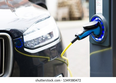 Electric new car plugged in for charging at outdoor station