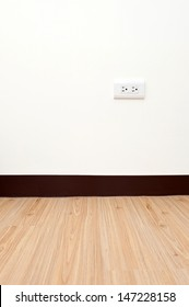 electric outlet on a white wall in a empty room with wooden floor