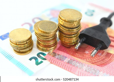 Electric plug with money and coins. Energy saving concept. Soft and selective focus.