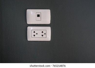 electric plug and telephone slot on dark gray wall - can use to display or montage on product