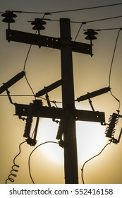 Electric pole silhouette against the sun
