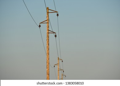 Electric pole and wires. An old overhead power line and single wood utility pole structure. Electrical power transmission and distribution cables. Vintage style with copy space.