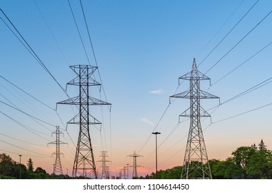 Electric poles and power lines in a  Canadian suburban area on a blue sunset sky background