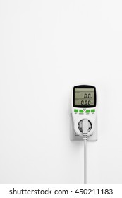 Electric power consumption meter isolated on white wall. Power saving concept or background.