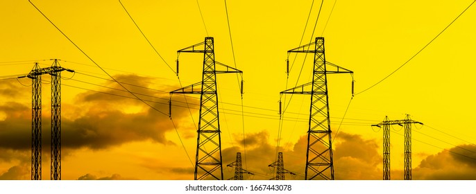Electric power industry. Transmission towers or electricity pylons with golden sky